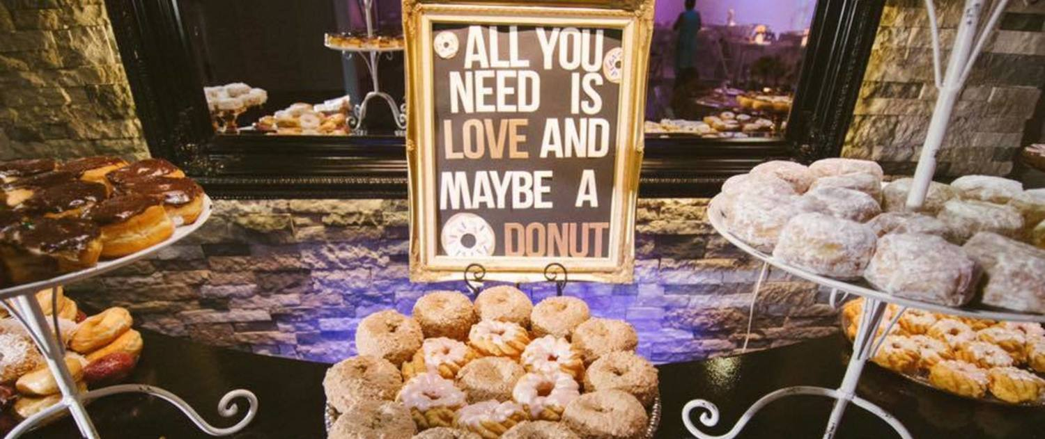 """All you need is love and maybe a donut"" sign on donut table"
