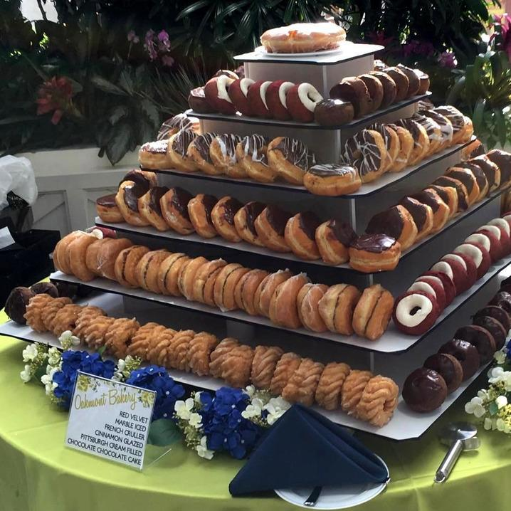 Huge square tiered tower with a variety of donuts