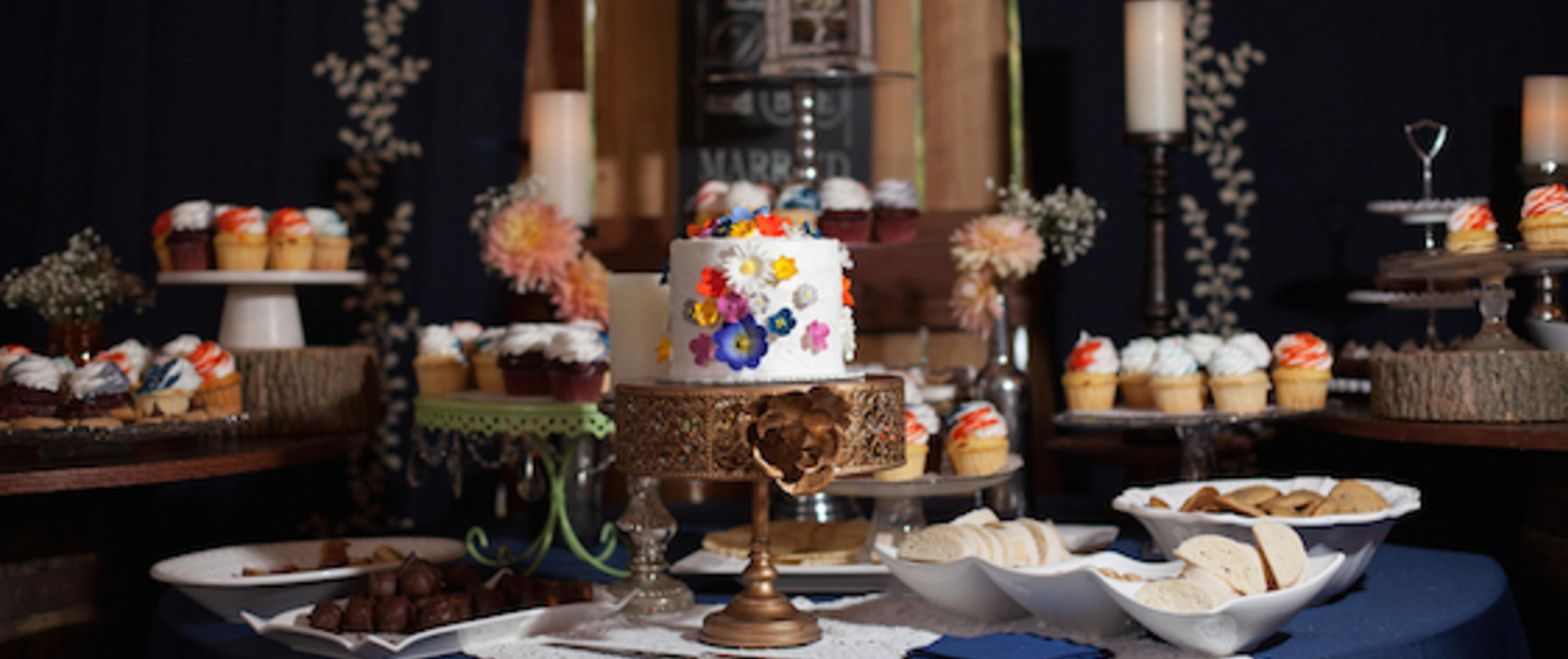 Fancy table setting with a miniature wedding cake and cupcakes
