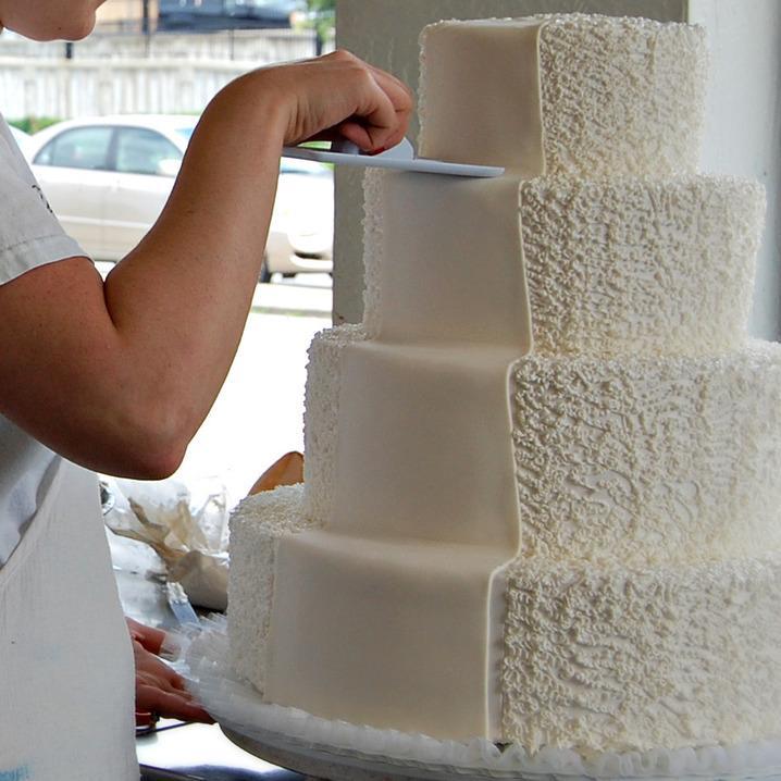 Cake decorator smoothing fondant onto a tiered cake