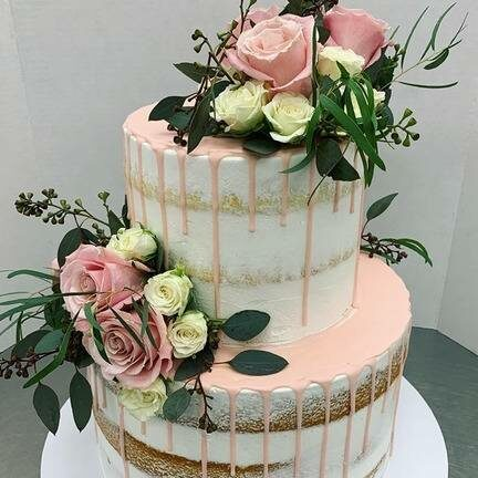 Pretty ppink and gold wedding cake with large flowers on it.