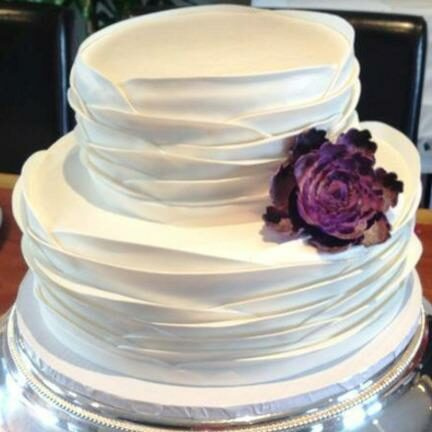 Tiered cake with ruffled icing and a purple flower